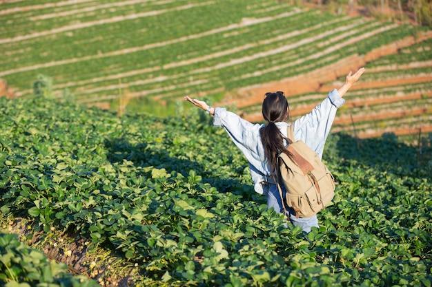 Vrouw spreidde armen in aardbeiboerderij