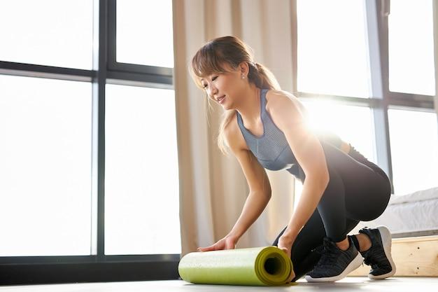 Vrouw spreidt de yogamat uit, ze gaat thuis trainen. vrouw in sportieve kleding bezig met sport overdag.