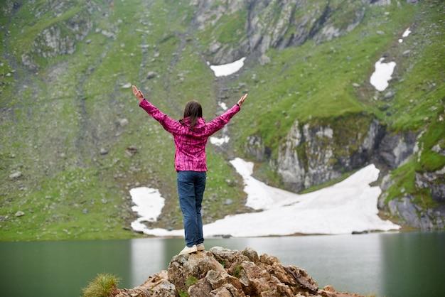 Vrouw spreidt haar armen opgewonden genietend van een prachtig uitzicht op het vidraru-meer