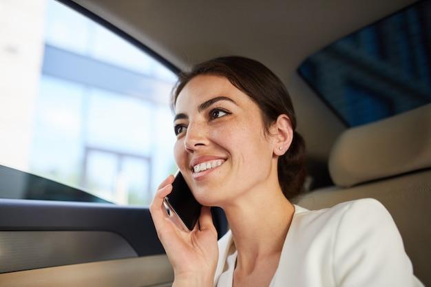 Vrouw spreken door smartphone in auto