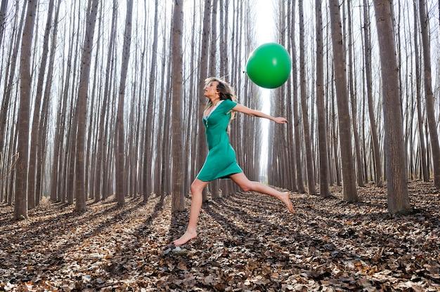 Vrouw springen met een groene ballon in het bos