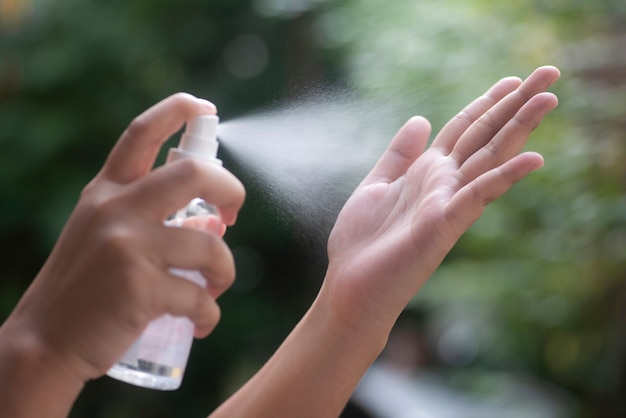 Vrouw sproeien antiseptisch op handen close-up, selectieve aandacht zijaanzicht spray desinfectie, bescherming, preventie, covid-19