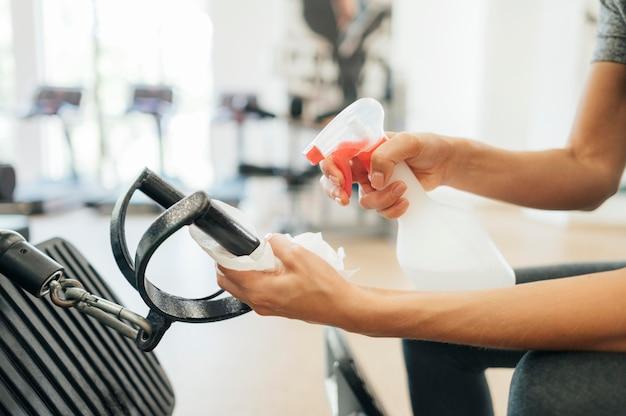Vrouw sproeien ontsmettingsmiddel op fitnessapparatuur