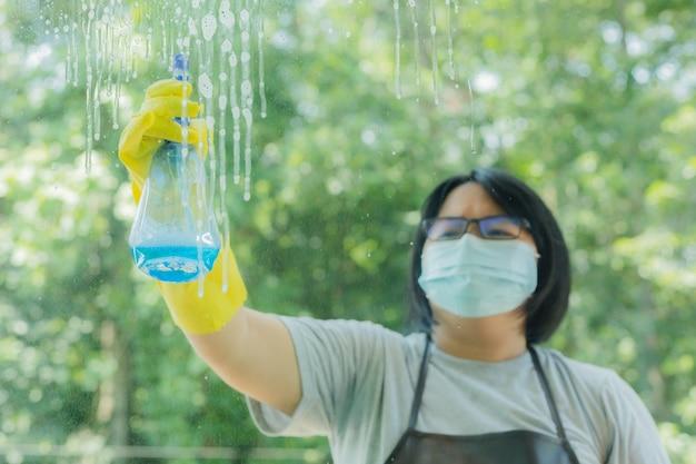 Vrouw sproeit en veegt glas af