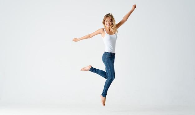 Vrouw sprong op een lichte achtergrond in volle groei sport fitness. hoge kwaliteit foto