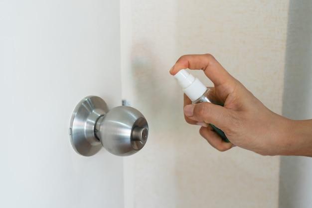 Vrouw spuit alcohol op deurknop voor bescherming tegen besmettelijke virussen, bacteriën en ziektekiemen.