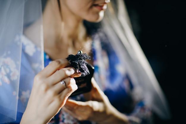 Vrouw spuit parfum op zichzelf