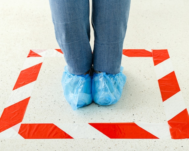 Vrouw staan in de rij sociale afstand houden overschoenen, medische schoenovertrekken dragen in winkel, supermarkt, ziekenhuis.