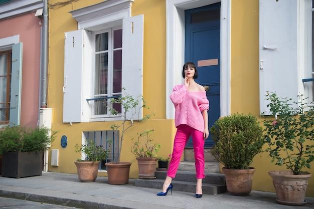 Vrouw staan in hoge hakken in parijs, frankrijk, vakantie. vrouw in roze trui, broek op straat, mode. schoonheid, uiterlijk, make-up. mode, stijl, mode. vakantie, reizen, reislust.