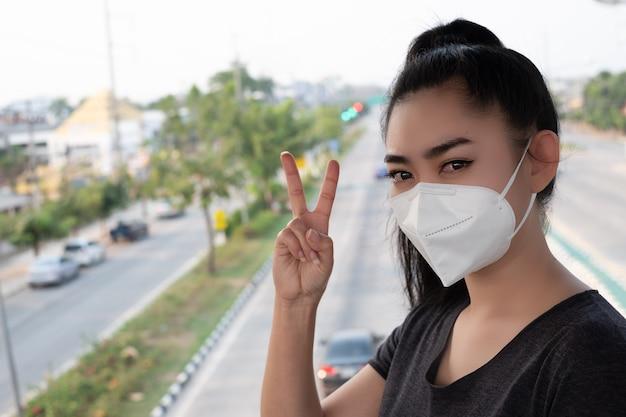 Vrouw staand handteken van 2 vingers met het opzetten van een gasmasker n95-masker