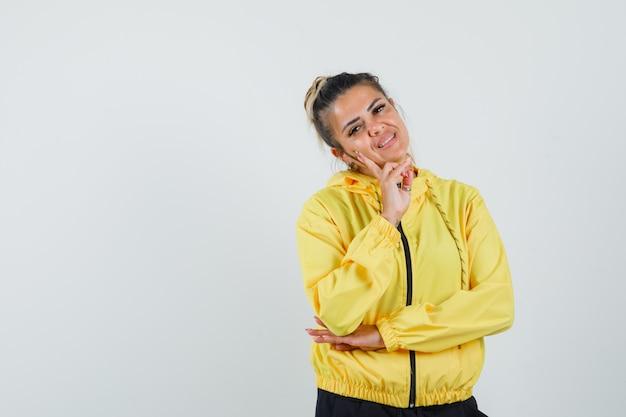 Vrouw staande in denken pose in sport pak en kijkt schattig, vooraanzicht.
