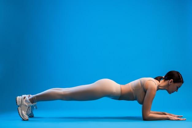 Vrouw staande in onderarmen plank pose op blauwe muur