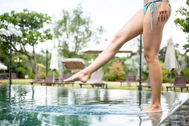 Vrouw staande op de pool rand en aanraken van water