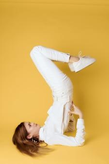 Vrouw staande op haar rug met haar benen ondersteboven geheven gouden achtergrond