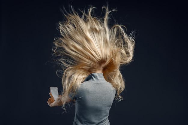 Vrouw staande tegen krachtige luchtstroom, achteraanzicht