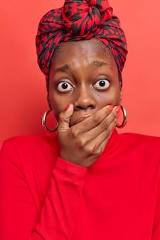 Vrouw staart afgeluisterde ogen tegens mond met hand draagt gebonden sjaal op hoofd casual coltrui geïsoleerd op levendig rood