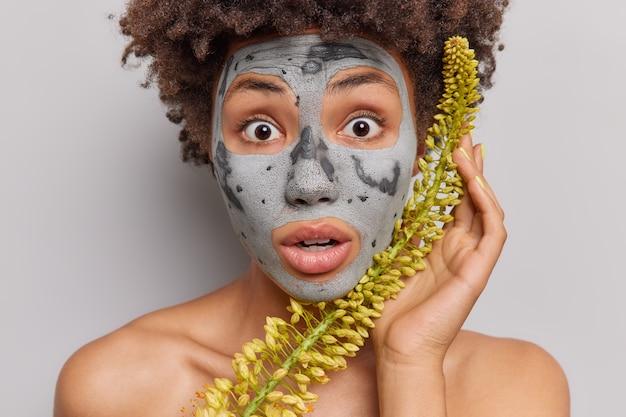 Vrouw staart onder de indruk naar camera past klei kruidenmasker toe kan niet geloven dat haar ogen topless binnen op grijs staan