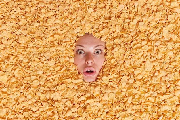 Vrouw staart onder de indruk omringd door droge ontbijtgranen heeft aandachtige blik voelt bang eet gezond voedsel wil een heerlijke snack als ontbijt