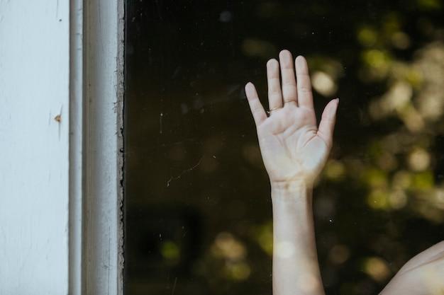 Vrouw staart uit het raam tijdens een lockdown.