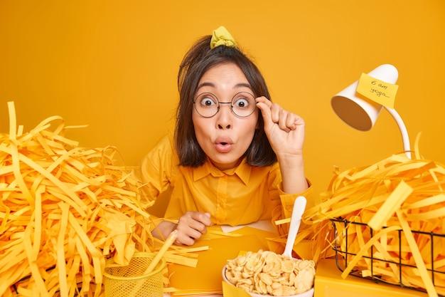 Vrouw staart verbaasd door ronde bril kan niet geloven in schokkend nieuws werkt thuis kantoor omringd door stapels pf papier heeft cornflakes als ontbijt