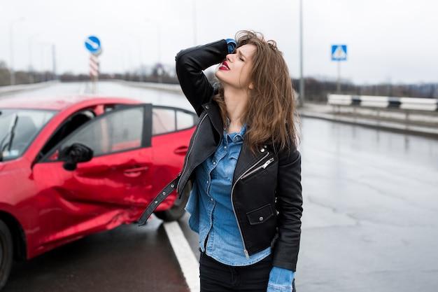 Vrouw staat bij een kapotte auto na een ongeval. roep om hulp. autoverzekering