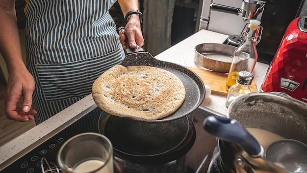 Vrouw staat bij het fornuis en bakt pannenkoeken in een hete pan