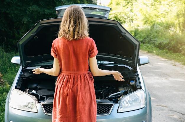 Vrouw staat in de buurt van de kapotte auto in de natuur. ongevalsituatie tijdens het reizen. meisje in jurk weet niet wat te doen. open de motorkap van het voertuig.
