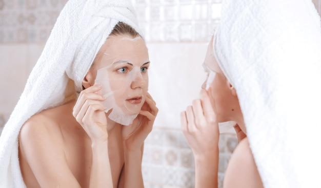 Vrouw staat in de buurt van een spiegel met een handdoek op haar hoofd en zet een cosmetisch masker op