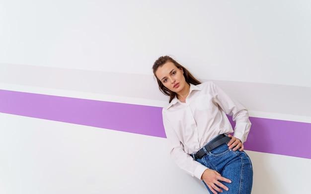 Vrouw staat in de buurt van witte muur met violette streep. blauwe spijkerbroek en wit overhemd. handen op taille en heupen. modieuze meid.