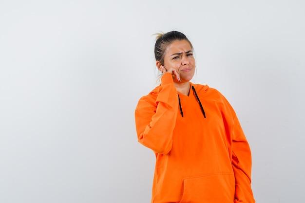 Vrouw staat in denkende pose in oranje hoodie en kijkt van streek