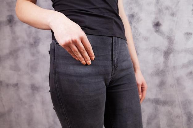 Vrouw staat in donkere spijkerbroek op een grijze