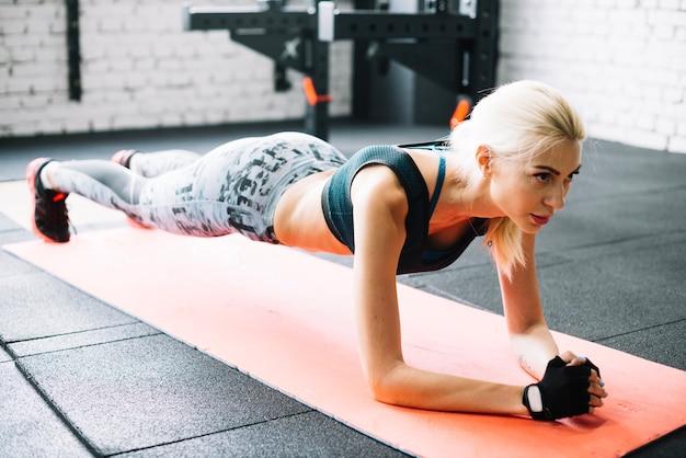 Vrouw staat in plank positie