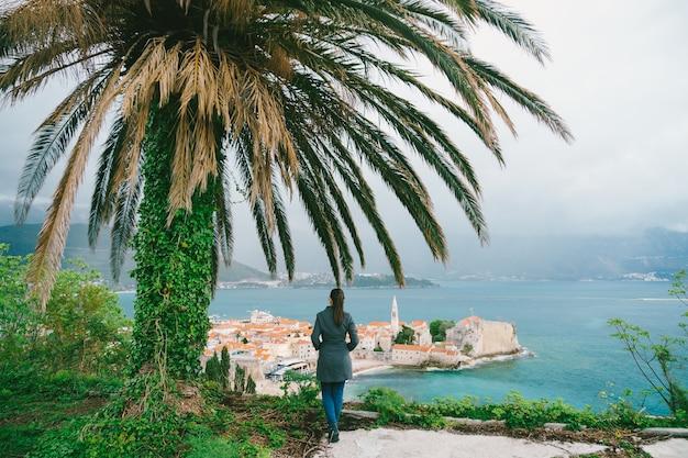 Vrouw staat onder een palmboom met haar rug naar de camera en kijkt naar de oude stad budva