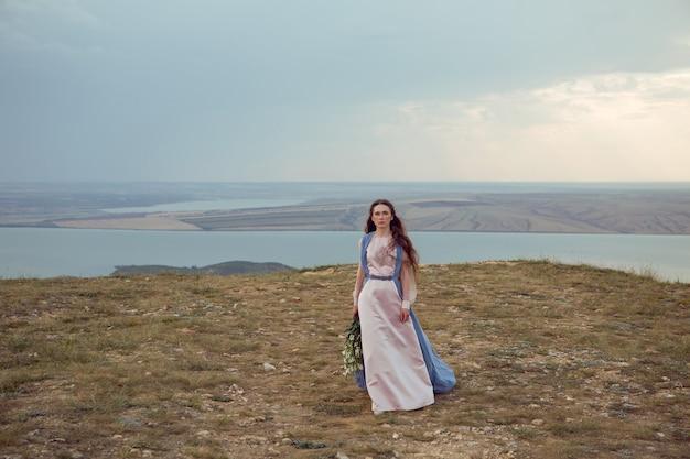Vrouw staat op een bergklif in een blauwe lange jurk in de zomer