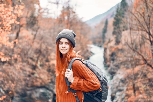 Vrouw staat op een brug over een rivier in de bergen herfst bos reizen