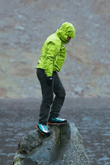 Vrouw staat op een gladde rots onder de regen