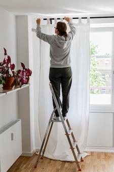 Vrouw staat op een trapladder bij het raam en hangt witte gordijnen aan de gordijnroede