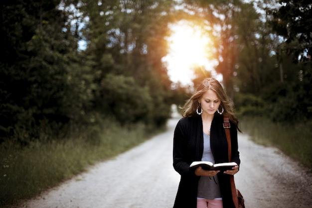 Vrouw staat op een weg tijdens het lezen van de bijbel met de zon