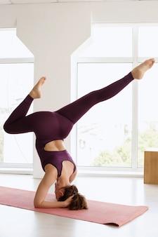 Vrouw staat op haar hoofd in asana. yoga day. yoga sportkleding