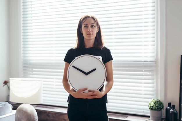 Vrouw staat op het bureaublad en houdt een horloge vast.