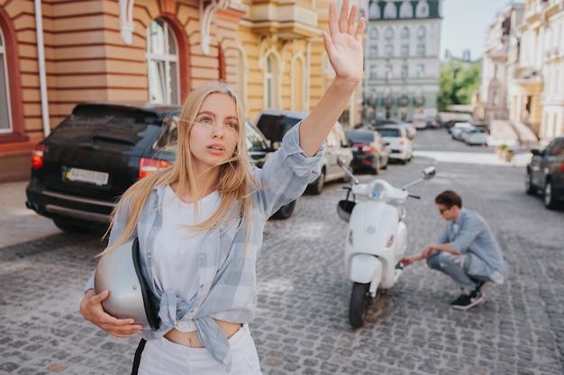 Vrouw staat op weg en zwaait met haar hand
