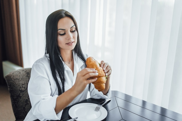 Vrouw staat 's ochtends aan het ontbijt met croissant