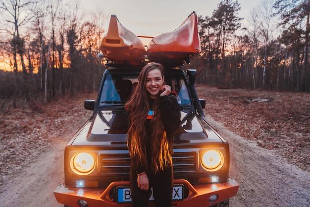 Vrouw staat vooraan van 4x4 terreinvoertuig