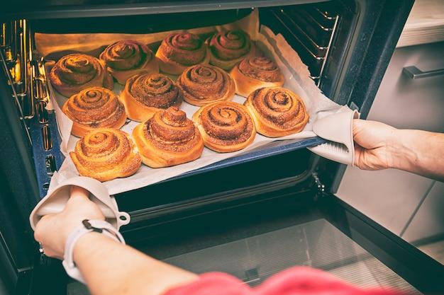 Vrouw stapt deco met verse bakkerij uit oven