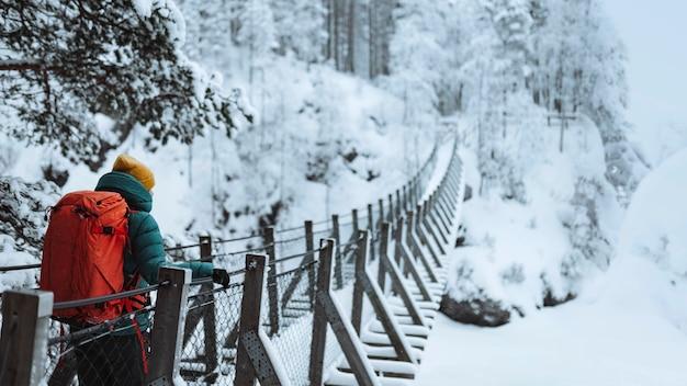 Vrouw steekt een hangbrug over in een besneeuwd bos, finland