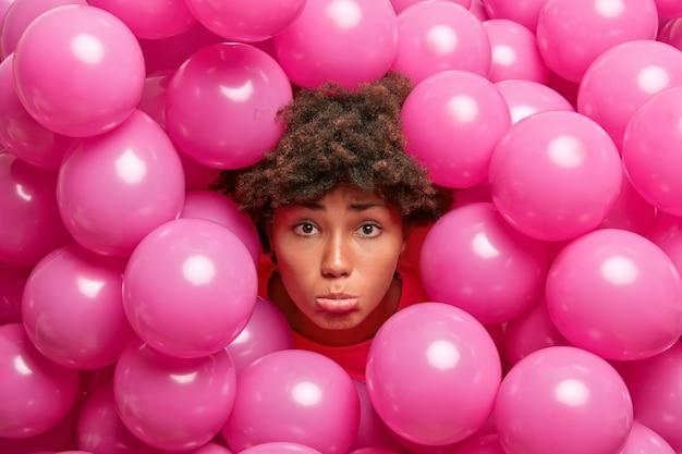 Vrouw steekt hoofd door opgeblazen ballonnen kijkt verdrietig sad