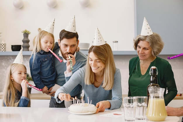 Vrouw steekt kaarsjes aan op de verjaardagstaart oude vrouw en haar volwassen zoon blijven achter