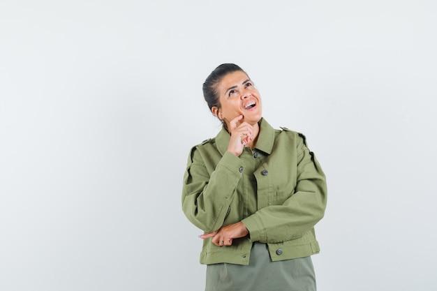 Vrouw steunt kin bij de hand in jas, t-shirt en kijkt gelukkig