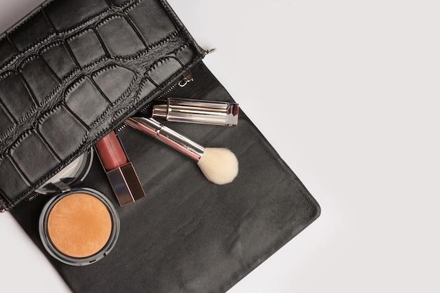 Vrouw stijl concept: vrouwelijke leren tas met bronzer, borstel en lippenstift uitvallen op een grijze achtergrond. lege ruimte