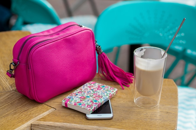 Vrouw stijlvolle accessoires op tafel in café, lente zomer modetrend